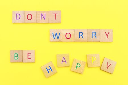 Dont worry be happy, words laid with multi colored letter platelets on a yellow background