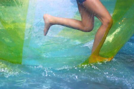 legs running in a water walking balloon Фото со стока