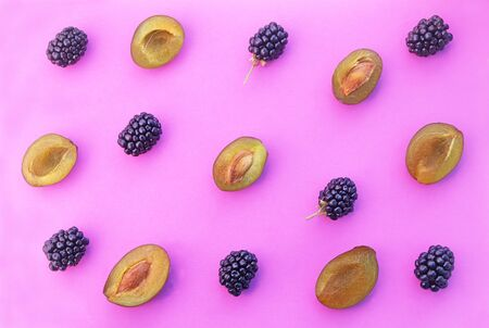 plums and blackberry-fruits on a pink background, pattern or background with autumn fruits Stockfoto
