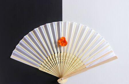 abanico decorativo blanco con empuñadura de madera y flor de color naranja sobre papel blanco y negro Foto de archivo