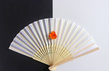 decorative white hand fan with a wooden grip and an orange colored blossom on black and white paper