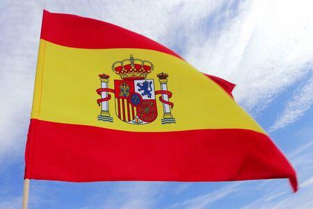 Close-up de una bandera española ondeando en el viento frente al cielo azul y blanco Foto de archivo