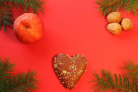 red christmas greeting card with a gingerbread heart, walnuts, an apple and fir branches