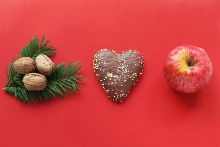 red Christmas border with gingerbread in heart shape, walnuts on a fir branch and a red apple