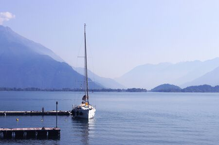sailing boat lying at a pier on a lake, misty mountains in the background Stockfoto