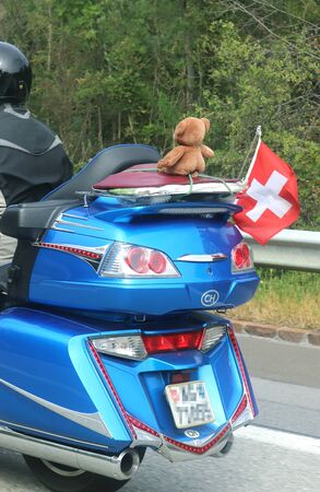 biker with a large blue motorcycle decorated with a Swiss lag and a teddy bear as a passenger, rear view Stockfoto
