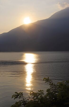 sunset at a lake, surrounded by mountains, golden hour
