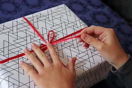 female hands wrapping or unwrapping a white and black gift pack on a table with a blue tablecloth