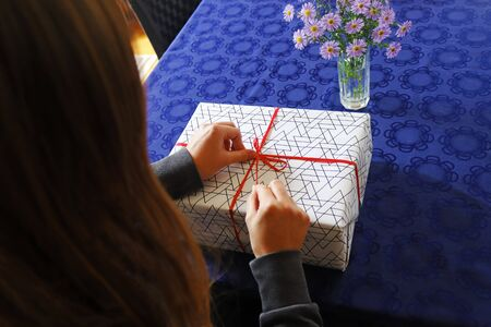young woman wrapping or unwrapping a gift pack on a table, rear view