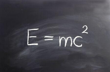 Einstein formula  E= mc2 written on a black chalkboard Stockfoto