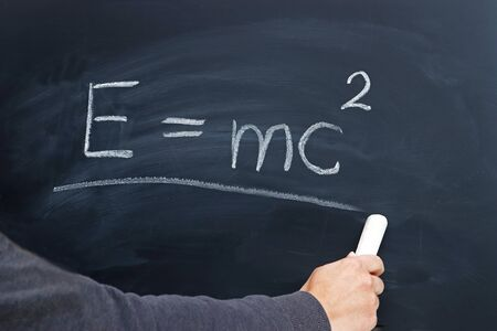 hand of a young person writing the Einstein formula on a blackboard with a chalk Stockfoto