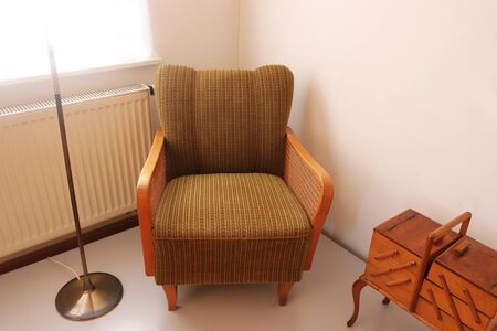 retro armchair with plaited armrest and retro wooden sewing box with legs from the sixties