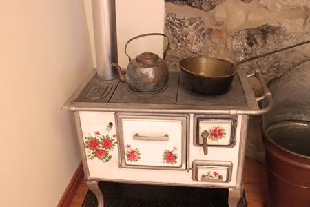old wood stove, retro kitchen object with kettle and copper pan