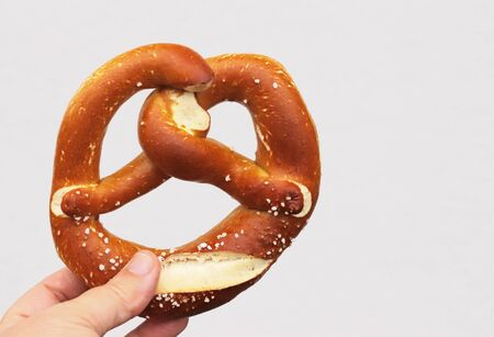 hand holding a fresh baked Bavarian pretzel in front of a bright background with copy space