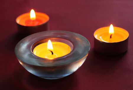 close-up of yellow and orange colored tealights burning  in front of a dark red background with copy space