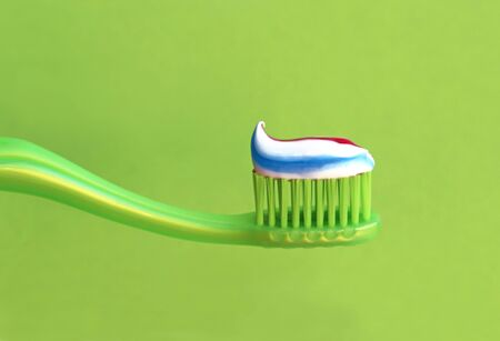 close-up of a green toothbrush with striped toothpaste in front of a green background with copy space Stockfoto