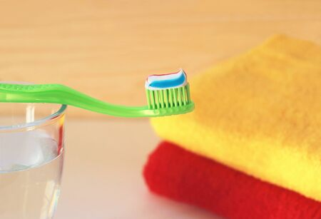 close-up of a green toothbrush with toothpaste on a glass of water, colorful towels in the background Фото со стока