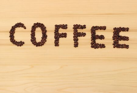 word coffee, built with coffee beans on a wooden table, background with copy space