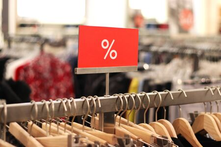 red percentage sign at a clothes rail in a department store, background with copy space