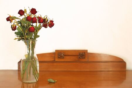 vase with withered red roses standing on an old wooden sideboard