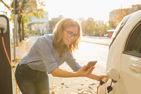 젊은 여자는 전기 자동차 근처에 서 있고 스마트 폰을 들고. 렌터카는 전기 자동차 충전소에서 충전 중입니다. 카 셰어 링. 스톡 콘텐츠