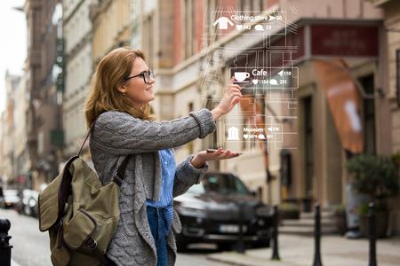 Realidad aumentada en marketing. Viajero mujer con teléfono. Navegación en la proyección de la pantalla Foto de archivo