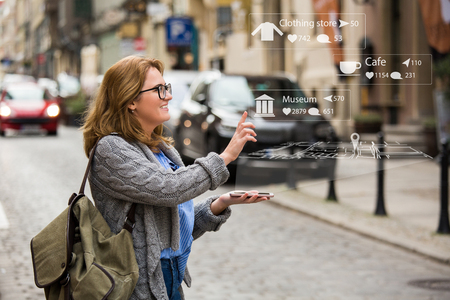 Augmented reality in marketing. Woman traveler with phone. Navigation on the projection of the display Standard-Bild