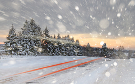 Winter road with snow showers. Taken with a slow shutter speed, you see the lights of a passing car. Copy space. Stock Photo