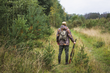 Hunter with a backpack and a hunting gun in the autumn forest. Stock Photo