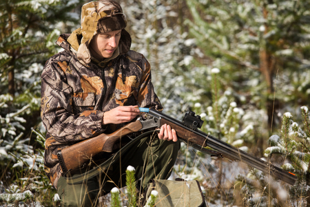 Hunter with a backpack and a hunting gun in the winter forest. Man is charging a hunting rifle. Winter snow-covered forest. Stock Photo