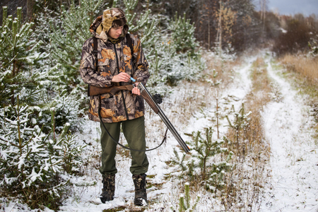snowcovered: Hunter with a backpack and a hunting gun in the winter forest. Man is charging a hunting rifle. Winter snow-covered forest. Stock Photo