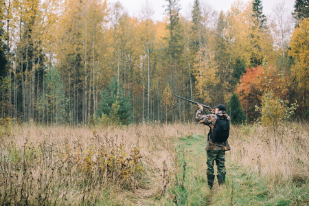 Hunter with hunting rifle in autumn forest Stock Photo