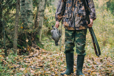 winchester: Hunter with hunting rifle and wildfowlin autumn forest