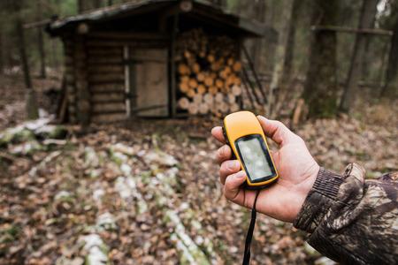 森の中の GPS ナビゲーターとハンターを男します。狩猟用のロッジ、バックパック、銃。テクノロジ、ガジェット。