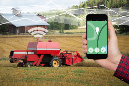 Hand with phone. On the screen control interface of the self driving combine harvester. Internet of things in agriculture