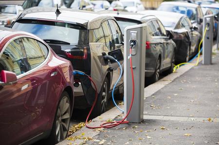 多くの電気自動車は、駐車場で充電ステーションによって充電されています。 写真素材