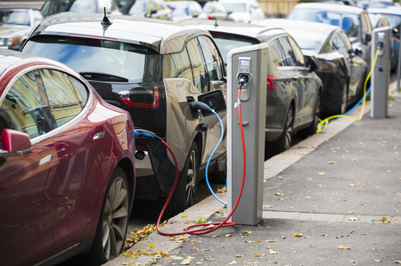 Many electric car are charged by charging stations in the parking lot. Stock fotó