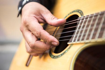 ギタリストはギターを弾きます。手のクローズアップ