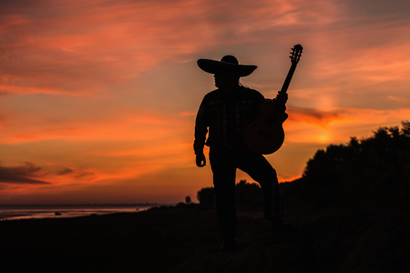 Mexican musician mariachi with a guitar. Silhouette on sunset background