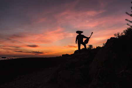 Mexican musician mariachi with a guitar. Silhouette on sunset background Stock Photo