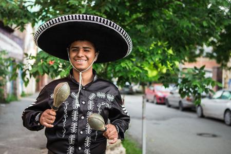 Mexicaanse muzikant in mariachi in traditionele klederdracht met maracas op straat Stockfoto
