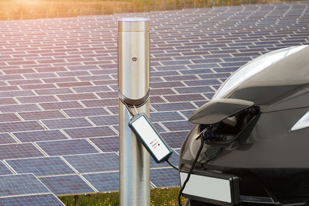 Electric car is charging near the station against the background of solar panels