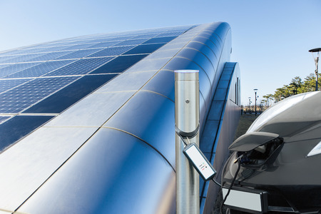 Electric car is charging near the station against the background of building with solar panels on roof
