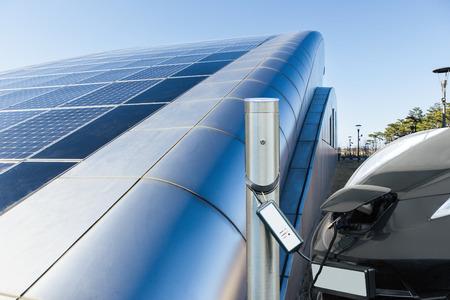 Elektroauto lädt nahe dem Bahnhof vor dem Hintergrund des Gebäudes mit Sonnenkollektoren auf Dach auf
