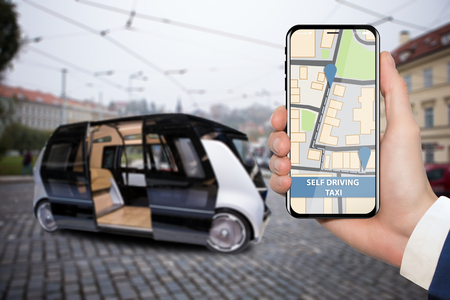 Control of self driving bus by mobile app. Hand with phone on a background of autonomous vehicle with open door. Фото со стока - 89552282