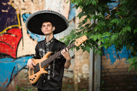 Mexican musicians in traditional mariachi costume with a guitar on the street Foto de archivo
