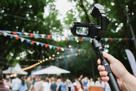 A mirrorless camera with a stabilized monopod and remote control. On the background of the fair in the park