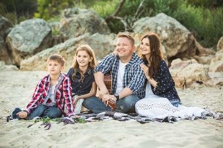 A family of four is sitting on a blanket. Father holds the guitar.