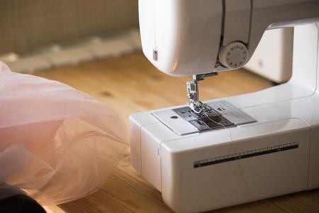 Designer de vestidos fazendo vestidos de casamento na máquina de costura Foto de archivo