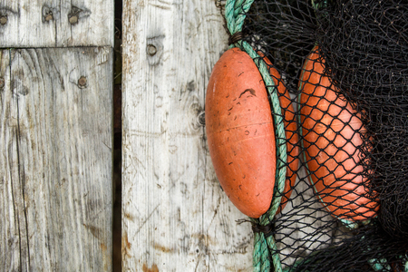 Many fishing nets and floats, stacked on a wooden dock.